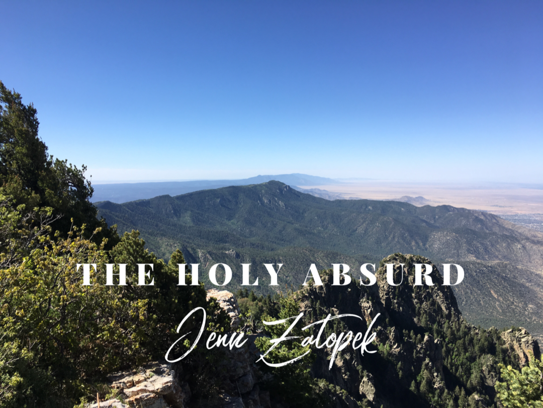 The words Holy Absurd against Sandia Mountains in New Mexico.