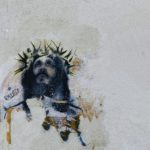 Graffiti art of Jesus with a crown of black thorns against a backdrop of light grey stone.