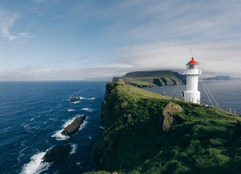 An image of a lighthouse on a cliff near the ocean on a sunny day.